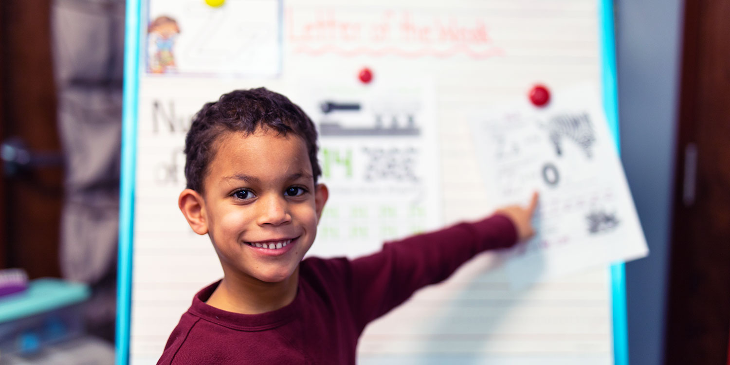 Smiling elementary student pointing to worksheet hanging up.