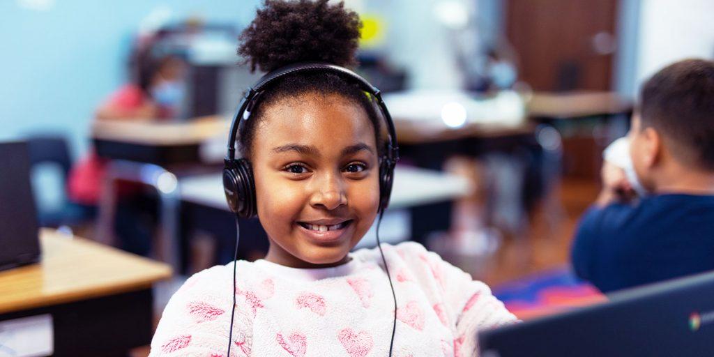 Smiling student wearing headphones at desk.