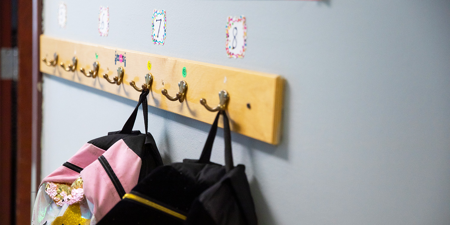 Wall rack with backpacks hanging up.