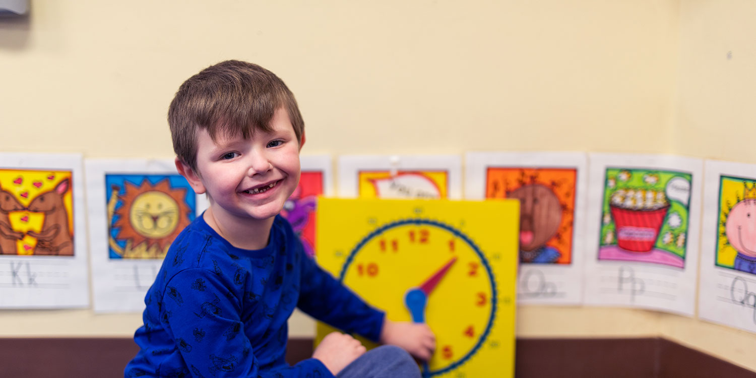 Smiling elementary student working with a clock.